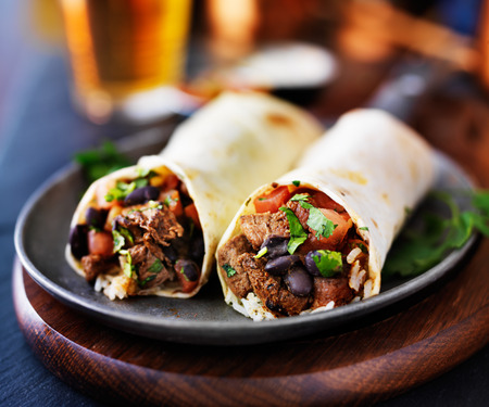 mexican beef burritos with beer in background Imagens