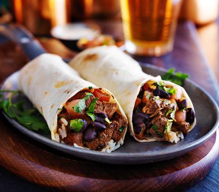 alubias: dos burritos de carne con arroz, frijoles negros y salsa Foto de archivo