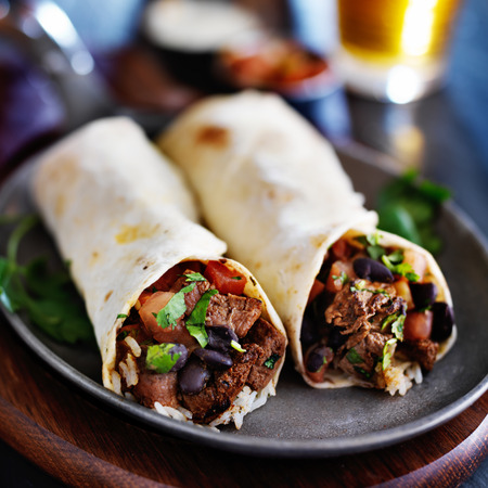 black dish: beef burritos with salsa, black beans, and rice Stock Photo