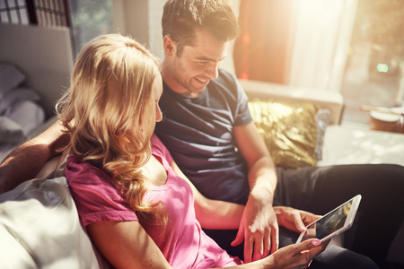 lifestyle: attractive couple utilisant comprimé ensemble o nfuton h à la maison
