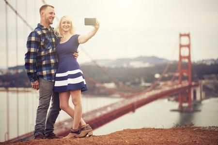 romance image: couple in taking selfie in front of golden gate bridge