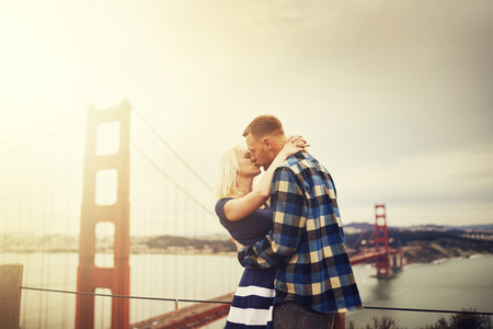 san francisco golden gate bridge: romantic couple kissing in front of golden gate bridge with lens flare and retro image filter