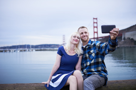 couple taking romantic selfie by golden gate bridge with copy space