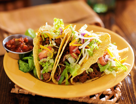close up food: platter of three beef mexican tacos with cheese and lettuce