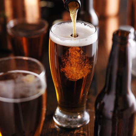 barra de bar: pourng cerveza de botella en el vidrio en el bar