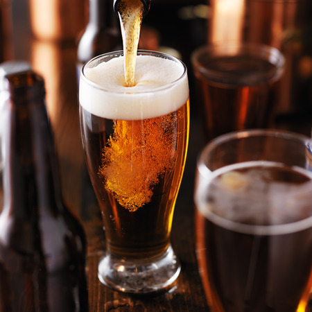 bar top: pouring beer into glass on wooden table Stock Photo