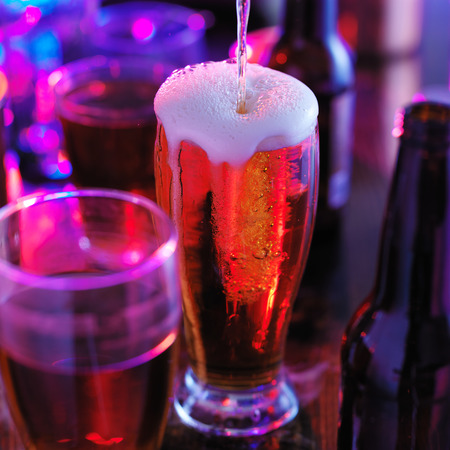 overflowing: pouring beer into overflowing glass with colorful lights at bar