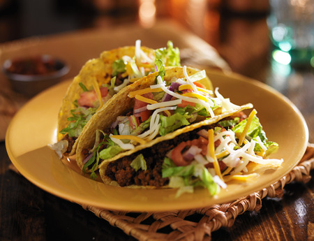 close up food: plate of tacos with yellow hard shells and beef