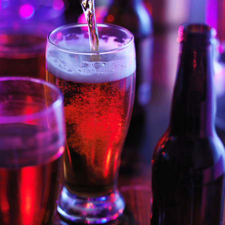 beer pouring into glass at colorful night club Stock Photo