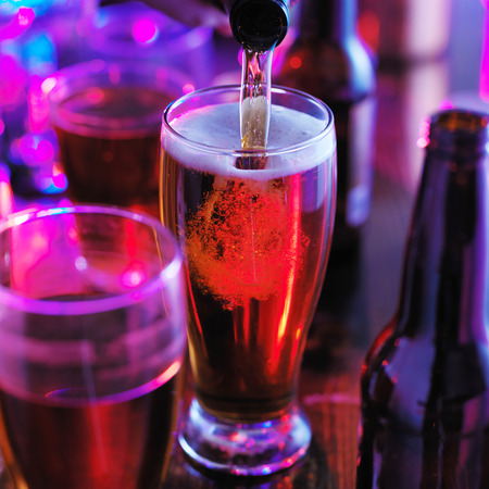 bar top: pouring beer into pint glass with colorful lighting at pub or bar Stock Photo