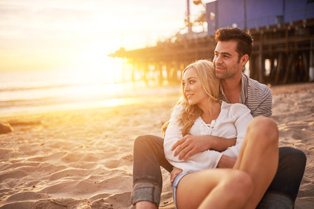 couple cuddling: romantic couple having fun at santa monica on beach