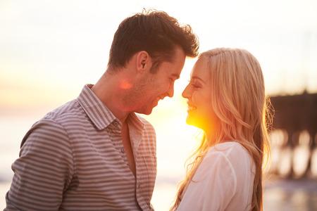 femme romantique: couple romantique au coucher du soleil sur le point d'embrasser
