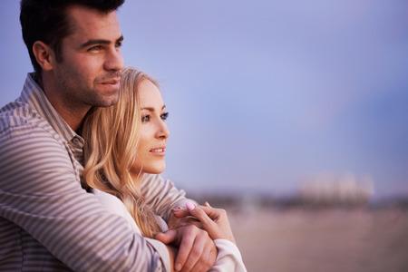paar op strand bij schemering op zoek naar buiten