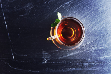 top down: glass of tea viewed from over head on slate Stock Photo