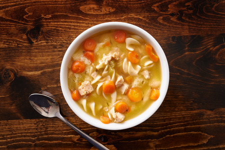 vegetable soup: bowl of chicken noodle soup shot top down