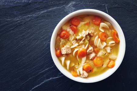 meat soup: top down photo of chicken noodle soup with copy space on slate Stock Photo