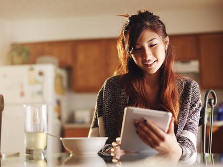 asiatisches jugendlich Mädchen mit Tablette zum Frühstück