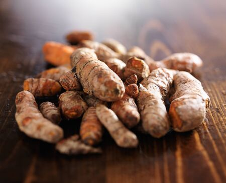 pile of fresh turmeric roots on wooden table with copyspace Stock Photo