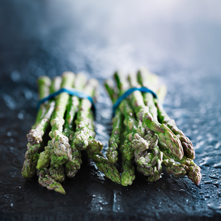 bunched: fresh asparagus in two bunchess on slate with copy space Stock Photo