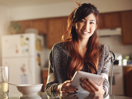 happy teenagers: asian teen using tablet at breakfast portrait Stock Photo