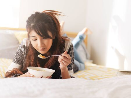 asian teenager eating chicken soup in bed