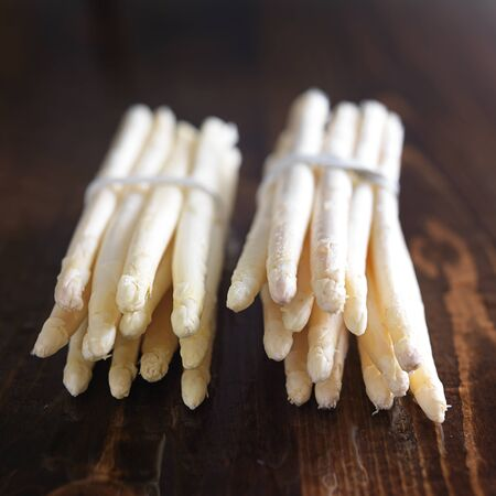 bunched: two bunches of white asparagus on wooden table