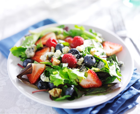 berry salad with walnuts and blue cheese on white table cloth