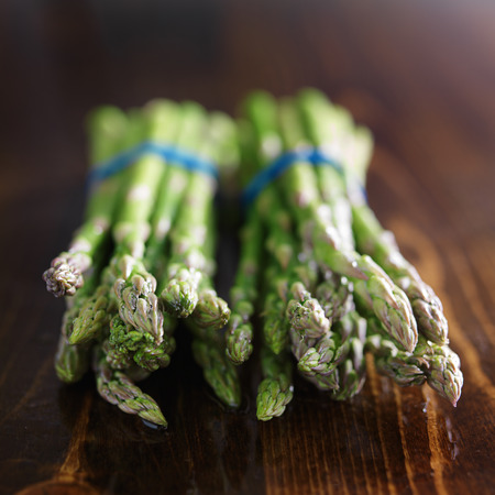 bunched: two bunches of asparagus on wooden table top