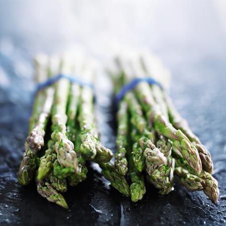 bunched: asparagi freschi in due grappoli sulla superficie di ardesia
