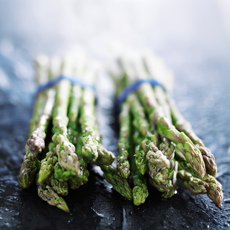 bunched: fresh asparagus in two bunches on slate surface