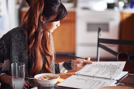 Aziatische tiener huiswerk op keukentafel