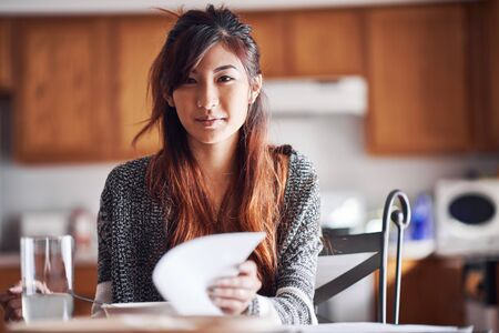 turning table: asian teen girl with homework in kitchen