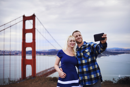 romantic couple taking selfies in front of golden gate bridge photo