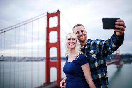romantic couple taking selfie by golden gate bridge with film grain filter photo
