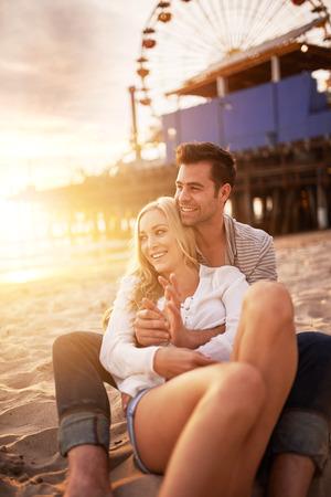 paar zitten in het zand op het strand in de buurt van de Santa Monica Pier in Californië bij zonsondergang Stockfoto