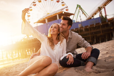 romantic places: happy romantic couple taking selfie at santa monica Stock Photo
