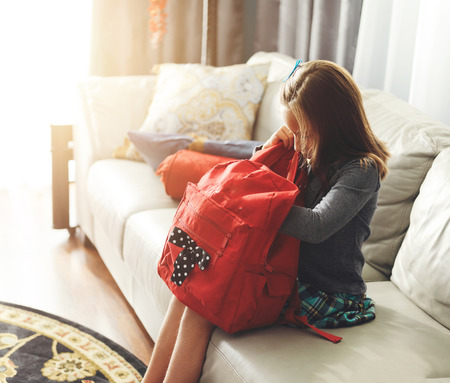 little girl getting ready for school looking in backpack Stock Photo