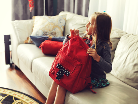 小さな女の子の学校のバックパックに見ているの準備
