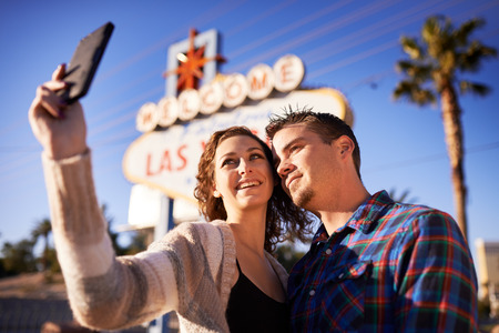 romantic couple taking selfie in front of welcome to las vegas sign
