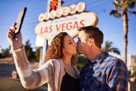 romantic kiss: couple kissing and taking selfie in front of welcome to las vegas sign