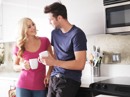 resting: happy couple drinking coffee together in kitchen