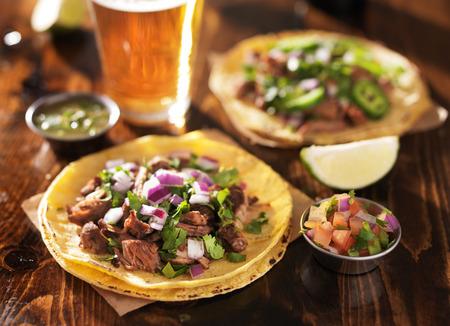 alimentos y bebidas: aut�nticos tacos mexicanos con cerveza en mesa de madera Foto de archivo