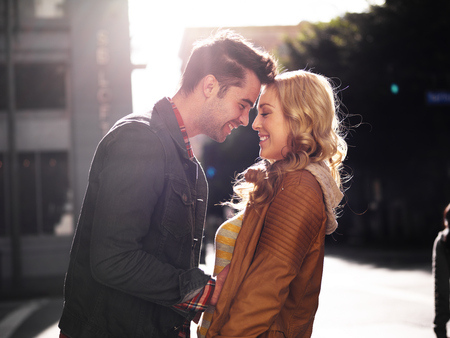 man woman hugging: couple on street in city flirting with lens flare