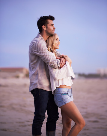 couples hug: two romantic lovers on the beach at twilight Stock Photo