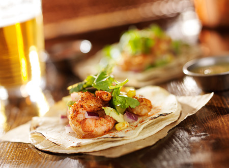 glass table: spicy shrimp avocado tacos in slanted composition