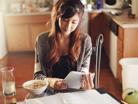 tablet: asian girl with tablet eating breakfast
