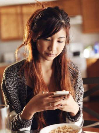 savvy: asian girl using smart phone in kitchen at breakfast