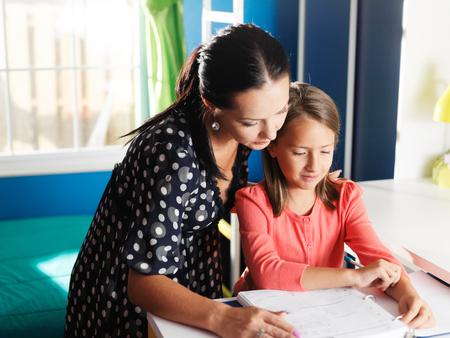 Niños ayudando: madre e hija haciendo la tarea juntos Foto de archivo