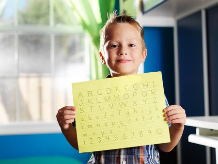 little boy holding completed homework Stock Photo
