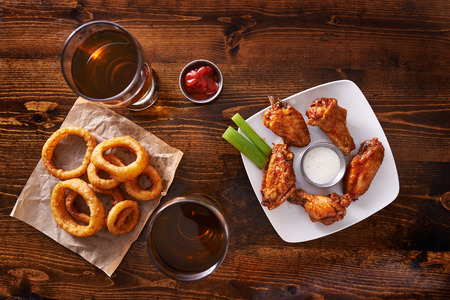 fried chicken wings: appetizer sampler with onion rings and chicken wings shot top down